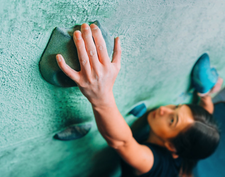 to climb: Young woman climbing up on wall in gym, focus on hand Stock Photo
