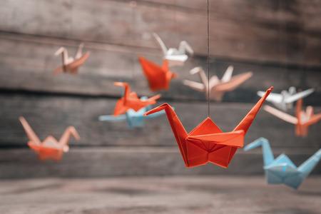 Bunte viele Origami Kraniche aus Papier auf Holzuntergrund
