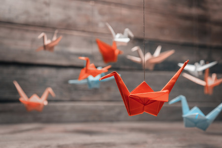 Colorful many origami paper cranes on wooden background Stockfoto
