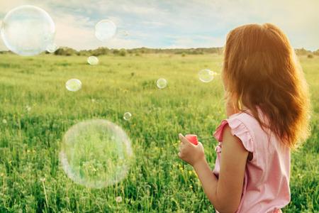 Klein meisje in jurk blaast roze zeepbellen op zomer weide op zonnige dag, achteraanzicht. Afbeelding met zonlicht effect Stockfoto