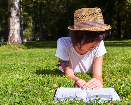Woman hipster lies on green grass and reads book against city park. photo