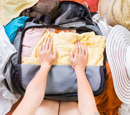 suitcase packing: Womans hands are packing clothes in a bag. Top view. Stock Photo