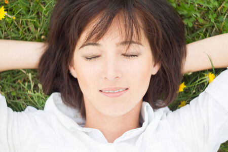 one eye closed: Young woman lying on a meadow with eyes closed, close-up