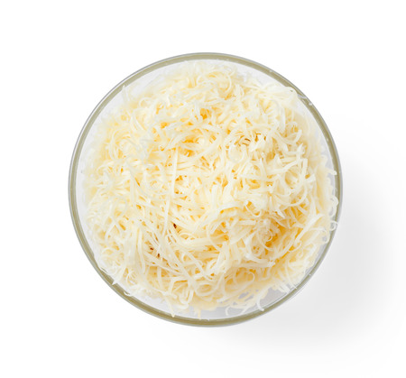 grated parmesan cheese: Bowl with grated cheese on a white background, top view. Stock Photo