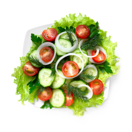 view top: Salad of cucumbers, tomatoes and greens on a white background, top view