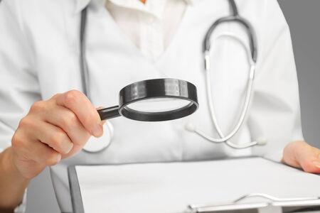 lupe: Doctor Looking Through Magnifying Glass On Gray Background. Space for text