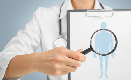 lupe: Unrecognizable doctor is showing clipboard with silhouette of a man under the medical magnifying glass Stock Photo