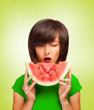 Fashionable young woman holding a slice of watermelon near the mouth photo