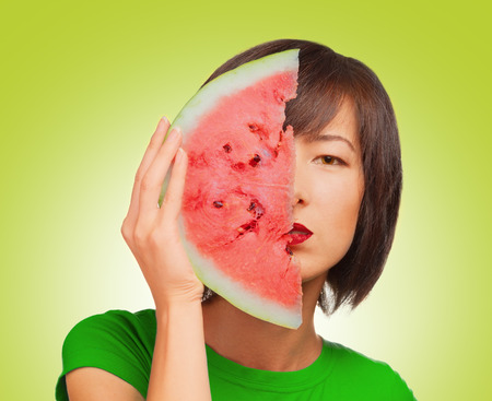 Attractive young woman covers half the face watermelon photo