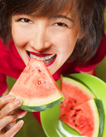 Young beautiful woman biting slice of watermelon, top view photo