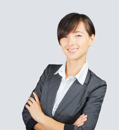gray suit: Happy business woman in a gray suit with arms crossed
