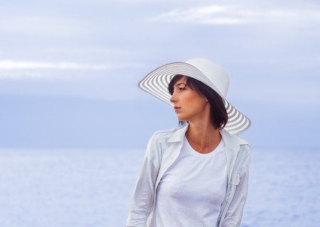 brim: Young woman in a hat with a wide brim stands on the the beach