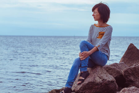 Young woman sitting on a rock by the sea photo