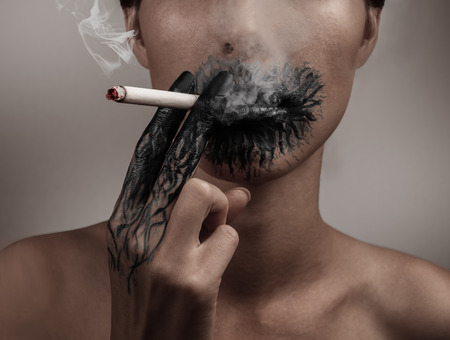 A woman smokes a cigarette, her hand and her mouth blackened, concept of a slow death from smoking Stock Photo