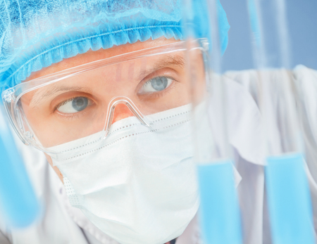 biotecnologia: Hombre técnico de laboratorio está mirando el tubo de ensayo con el líquido azul, primer plano