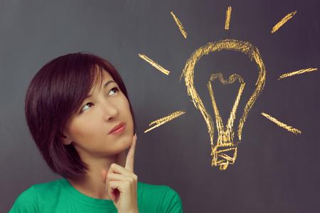 personas pensando: La mujer joven piensa en el fondo de la pizarra con la bombilla, el concepto de la nueva idea