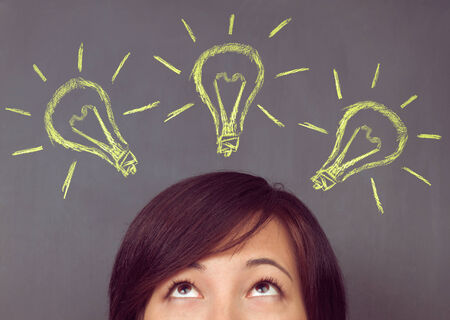 bulb light: Young woman looks up on light bulb on the background of blackboard, concept of new ideas