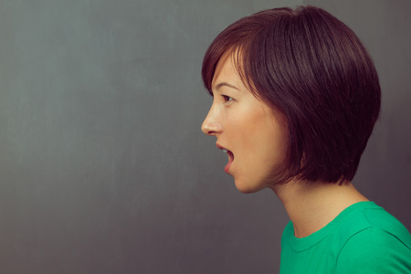 woman open mouth: Young woman yells on the background of school board, space for text, side view Stock Photo