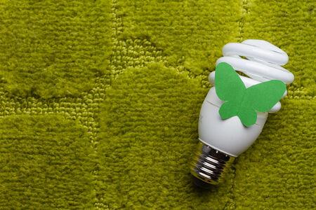 Energy saving bulb on a green background photo