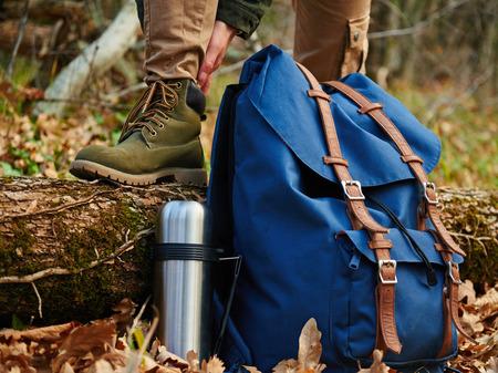 Vrouwelijke wandelaar draagt laarzen buiten in de herfst bos, vlakbij thermoskan en rugzak. Weergave van de benen. Wandelen en vrije tijd thema Stockfoto