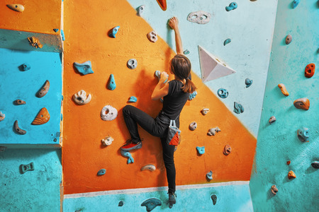 climbing: Young woman climbing up on practice wall in gym, rear view