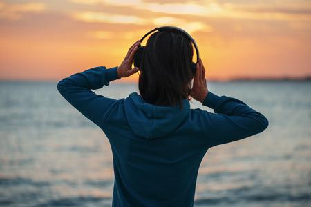 Jovem Irreconhecível nos auscultadores que aprecia belo pôr do sol sobre o mar, retrovisor Banco de Imagens