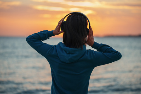 Unrecognizable young woman in headphones enjoying beautiful sunset over the sea, rear view 版權商用圖片