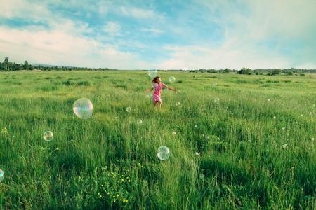 Happy little girl playing among soap bubbles on green meadow in summer Standard-Bild
