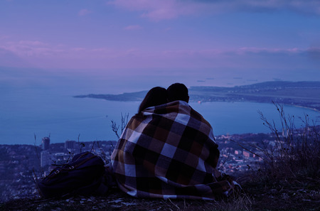 Young couple in love wrapped in plaid sitting on hill and looking at the city in night. Concept of tranquil life from the urban bustle photo