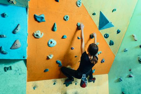 escalando: Mujer joven que sube para arriba en la pared en el gimnasio, de visi�n trasera Foto de archivo