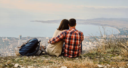 bustle: Young couple in love sitting on hill and looking at the city, rear view. Concept of tranquil life from the urban bustle Stock Photo
