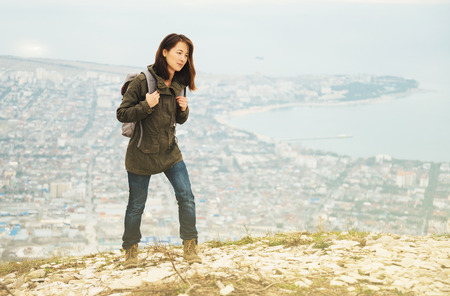 Young traveler woman with backpack walking in highlands over the city. Hiking and recreation theme photo
