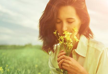 Mujer joven hermosa que huele las flores amarillas con los ojos cerrados en verano al aire libre. Imagen con el efecto luz solar