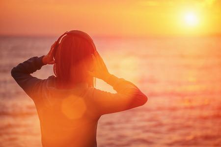 personas escuchando: Mujer joven en auriculares escuchando m�sica y disfrutando de hermosa puesta de sol