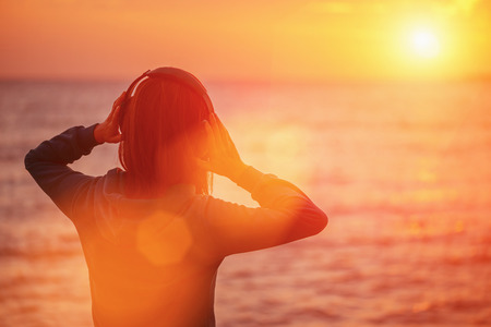 Young woman in headphones listening music and enjoying beautiful sunset