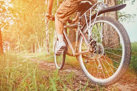 Nierozpoznany człowiek jazda na rowerze w parku latem w słoneczny dzień. Obraz z mocą światła słonecznego