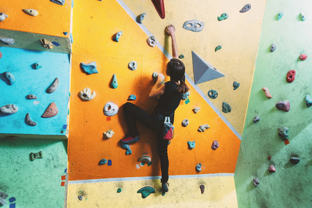 climber: Girl climbing up on practice wall in gym, rear view