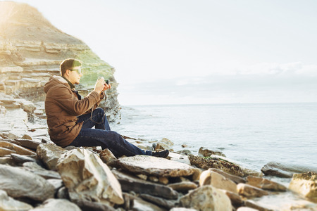 one young man: Traveler hipster young man takes photographs with vintage photo camera on coastline near the sea. Image with sunlight effect