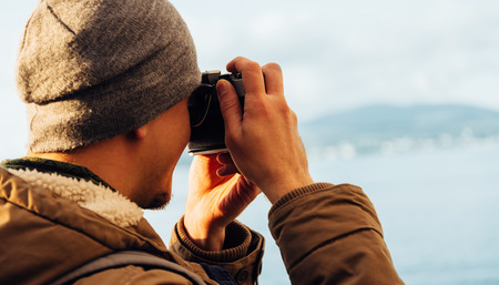 one young man: Traveler hipster guy takes photographs with vintage photo camera on coastline near the sea Stock Photo
