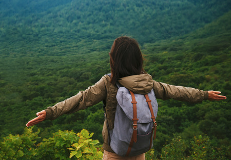 Freedom hiker woman standing with raised arms and enjoying beautiful landscape in summer