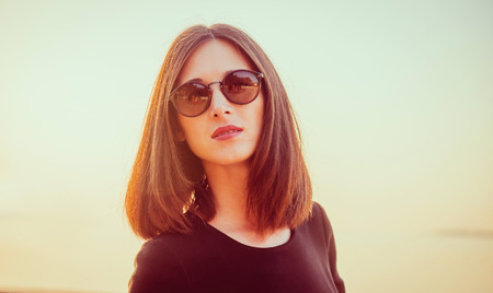 hair dress: Portrait of attractive brunette woman with long hair in sunglasses on background of sea at sunny day. Image with sunlight effect