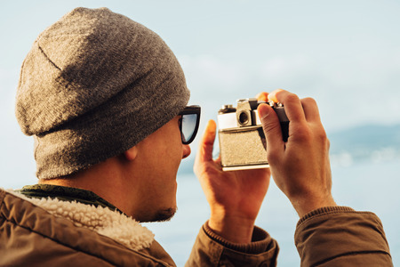 takes: Traveler hipster young man takes photographs with vintage photo camera on coastline near the sea