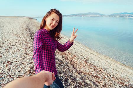 segno della pace: Coppia in amore. Sorridente giovane donna con la mano dell'uomo e mostrando segno di pace sulla spiaggia vicino al mare Archivio Fotografico