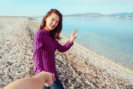 man holding sign: Couple in love. Smiling young woman holding mans hand and showing peace sign on beach near the sea