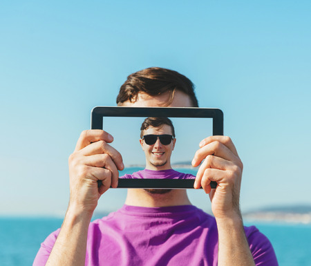 people and nature: Young handsome man doing a self-portrait with him digital tablet on background of sea