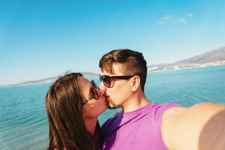 novios besandose: Feliz pareja de j�venes enamorados bes�ndose y teniendo autorretrato en la playa en el fondo del mar azul