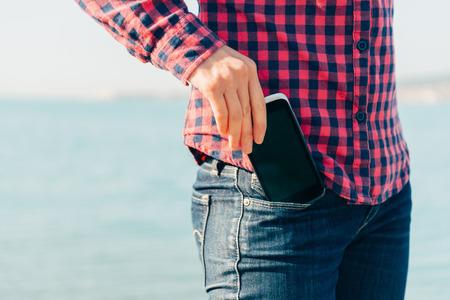 Vrouw neemt uit de mobiele telefoon van haar zak van jeans op het strand in de buurt van de zee naar zelfportret te maken of om de zee te fotograferen