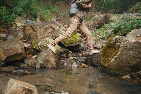 Hiker woman crossing a creek on stones in summer forest, view of legs 免版税图像