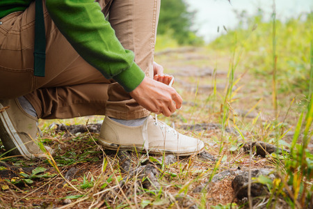 shoelace: Hiker woman tying a shoelaces in summer forest, face is not visible