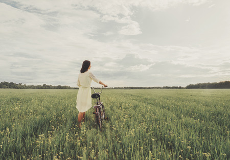 Beautiful young woman in dress walking with a bicycle on summer wildflower meadow.